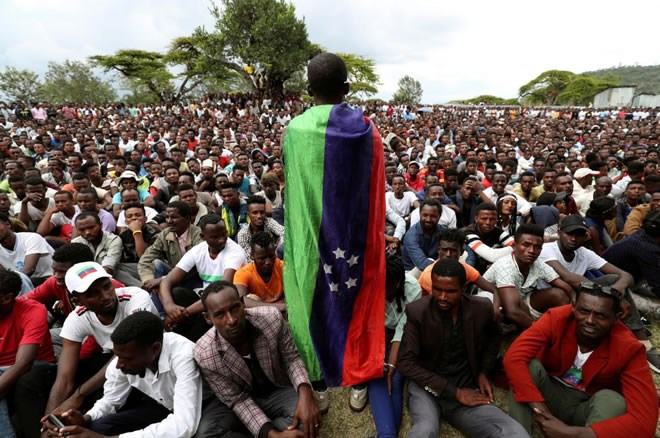 A sidama youth leader carrying a flag addresses people as they gather for meeting to declare their own region in Hawassa, Ethiopia July 17, 2019. REUTERS/Tisksa Negeri